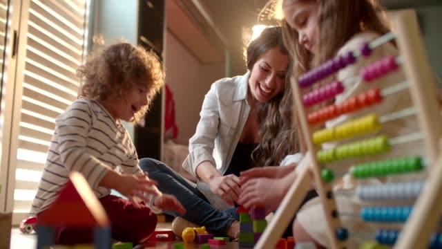 Cute-children-and-their-mother-excitedly-playing-with-toy-blocks