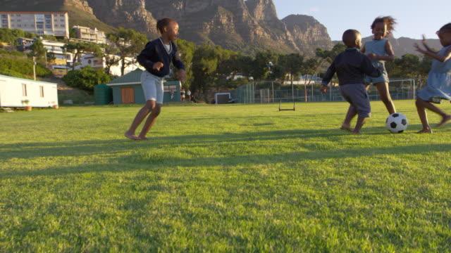 Elementary-school-kids-playing-football-in-a-field