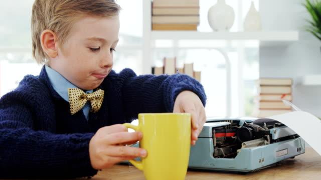 Boy-drinking-coffee-while-working-on-typewriter-4K-4k