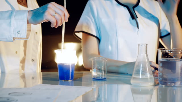 Professional-chemist-in-a-lab-coat-is-experimenting-by-mixing-liquid-chemicals-in-flasks-