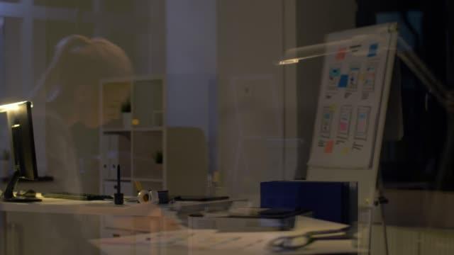 reflejo-de-pared-de-cristal-de-mujer-con-el-trabajo-en-la-oficina-de-la-noche