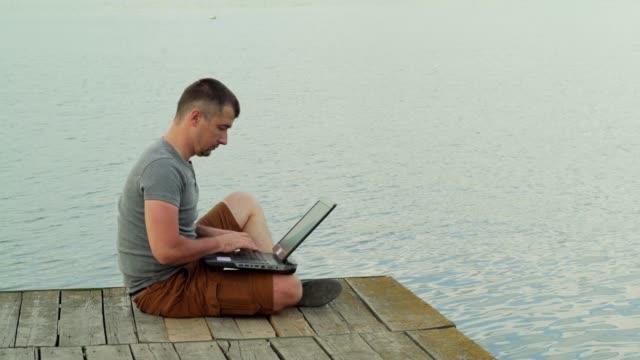 Vista-lateral-completo-de-sonriente-hombre-maduro-usando-laptop-en-muelle