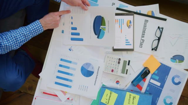 Overhead-Of-Businessman-Reviewing-Various-Financial-Graphs-At-Desk-4K