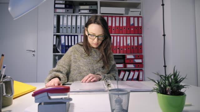 Woman-reading-through-files-in-ring-binder