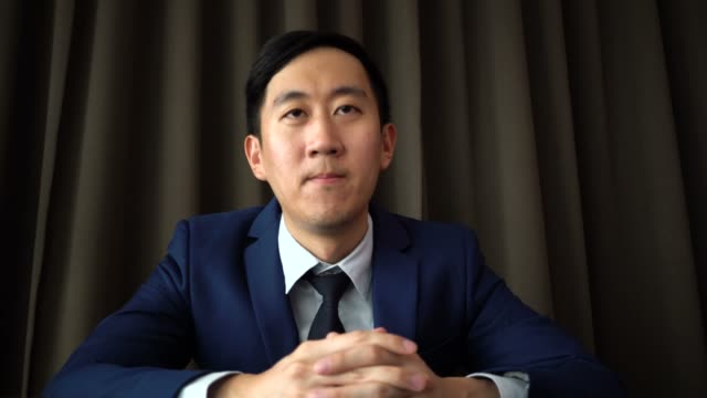 Young-Asian-business-man-speaking-on-the-video-call-conference-with-serious-look