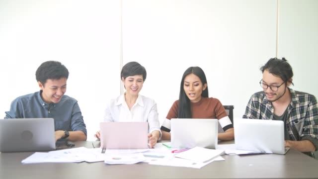 Reunión-de-negocios-Pequeño-en-marcha-reunión-de-negocios-en-la-habitación-Equipo-asiático-con-hombre-y-mujer-terminar-su-trabajo-y-celebrando-sentado-frente-a-cámara-Nuevo-modelo-de-negocio-en-marcha-conceptos-