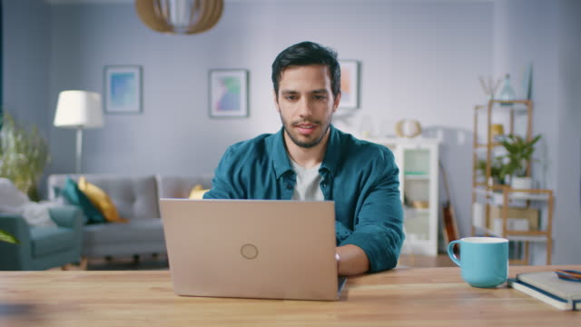 Medium-Shot-of-a-Handsome-Man-Sitting-at-His-Wooden-Desk-Working-on-a-Laptop-in-His-Cozy-Living-Room-