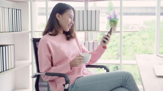 Schöne-intelligente-Business-Asiatin-in-intelligente-Freizeitkleidung-mit-Smartphone-und-trinken-warme-Tasse-Kaffee-sitzend-am-Tisch-im-Kreativbüro-Lifestyle-Frauen-arbeiten-bei-Bürokonzept-