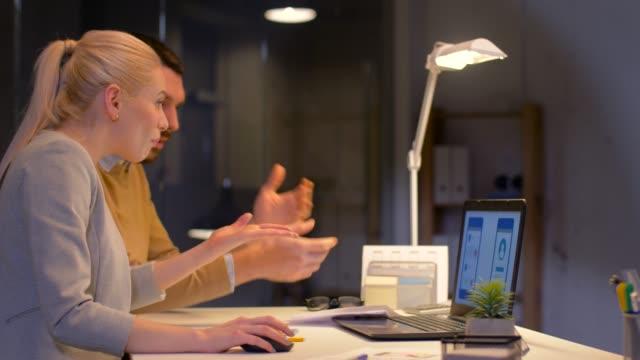 equipo-de-negocios-con-ordenador-portátil-a-trabajar-en-oficina-de-noche