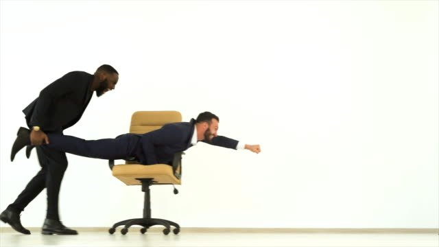 The-two-happy-businessmen-playing-with-an-office-chair-slow-motion