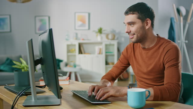 Handsome-Software-Engineer-Works-on-a-UX-/-UI-Mobile-App-Template-Uses-Personal-Computer-Freelance-Programmer-Working-from-Cozy-Living-Room-