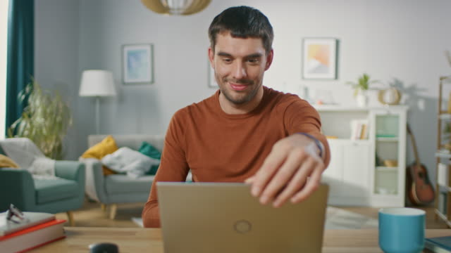 Confident-Young-Man-Sitting-at-His-Desk-at-Home-Opens-and-Starts-Using-Laptop-In-the-Background-Living-Room-with-Cozy-Design-
