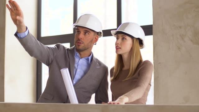 arquitectos-con-blueprint-y-cascos-en-oficina