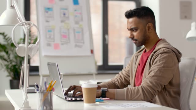 indian-creative-man-working-on-laptop-at-office