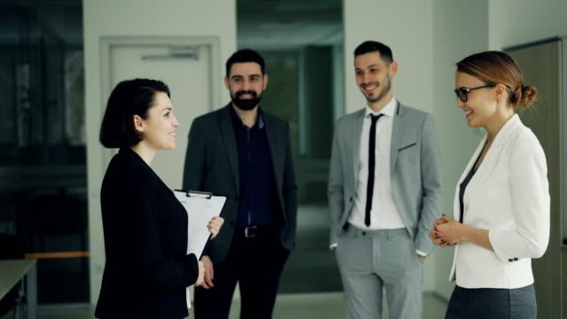 Bastante-joven-mujer-está-consiguiendo-trabajo-en-exitosa-empresa-estrechar-las-manos-con-CEO-y-sonriendo-mientras-que-otros-trabajadores-son-Palmas-de-las-manos-y-expresar-emociones-positivas-