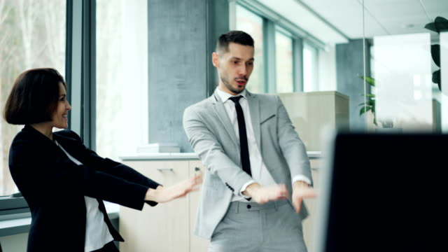 Careless-office-workers-are-relaxing-at-work-dancing-and-laughing-having-fun-together-moving-arms-and-bodies-Good-mood-happy-youth-and-workplace-concept-