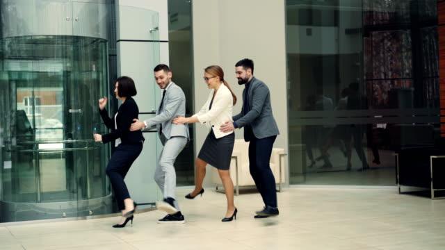 Spielerische-Kollegen-erfreuen-sich-Partei-am-Arbeitsplatz-Tanz-im-Foyer-zusammen-entspannen-und-Lachen-tragen-Anzüge-Informelle-Kommunikation-Glück-und-Team-Konzept-