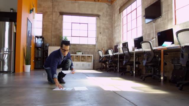 Designer-Plans-Layout-On-Floor-Of-Modern-Office-Shot-On-R3D
