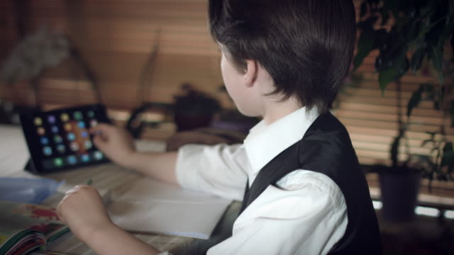 4K-Hi-Tech-Shot-of-a-Child-Doing-Homework-and-Searching-Tablet
