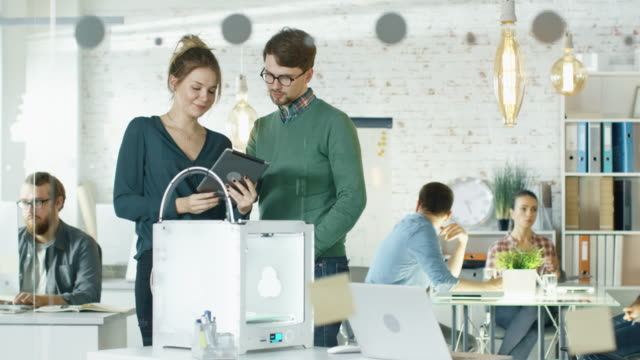 Beautiful-Creative-Girl-Shows-Tablet-Computer-To-Her-Stylish-Male-Colleague-They-Locate-in-a-Busy-Creative-Loft-Office-with-Young-People-Working-in-Background-