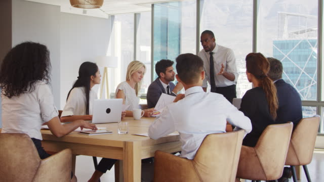 Businessman-Stands-To-Address-Meeting-Around-Board-Table