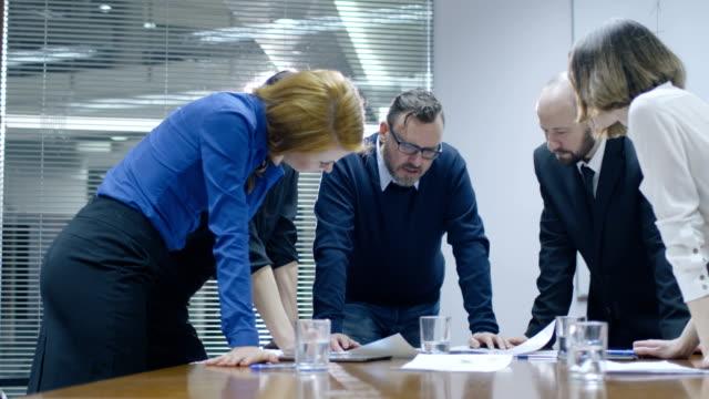El-empleado-está-haciendo-una-presentación-para-un-equipo-de-colegas-que-están-sentados-en-una-sala-de-reuniones-