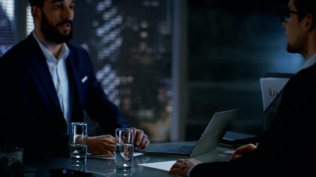 Spät-in-der-Nacht-Geschäftsmann-Geschäftsmann-hat-Gespräche-mit-wichtigen-Kunden-sie-kommen-zu-einer-Einigung-und-Hände-schütteln-Im-Hintergrund-große-Fenster-Blick-auf-Stadt-