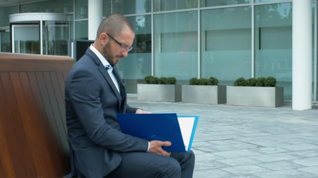 Ein-Geschäftsmann-Prüfung-wichtige-Unterlagen-vor-Bürogebäude
