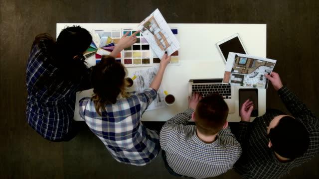 Dos-arquitectos-diseño-discutir-mientras-que-compañeros-de-trabajo-femenino-en-la-paleta-de-colores