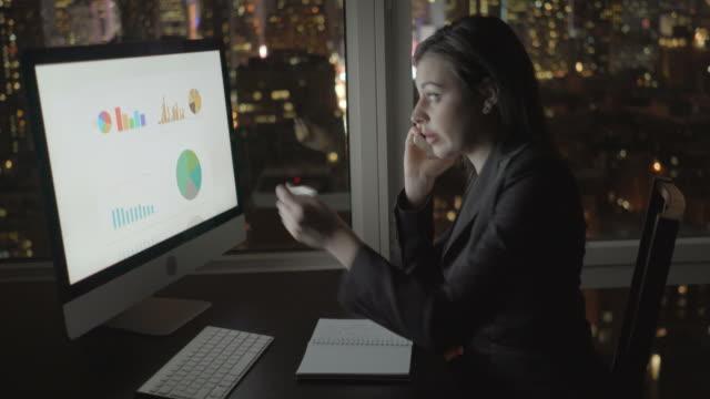 Attraktive-Brünette-am-Bürotisch-nachts-arbeiten-Geschäftsfrau-die-Arbeit-mit-Computer-und-Smartphone-mit-Stadtbild-Ansicht-im-Amt-