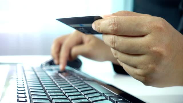 Primer-plano-de-manos-de-la-mujer-manteniendo-una-tarjeta-de-crédito-y-usando-equipo-para-ir-de-compras-en-línea-en-el-espacio-de-trabajo