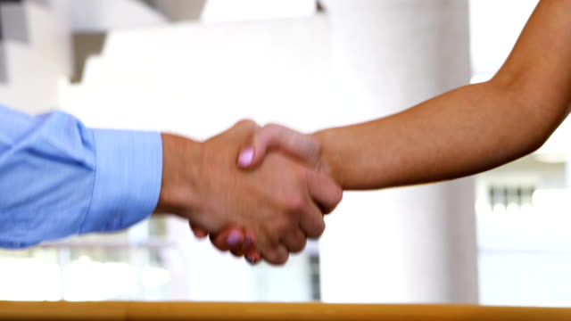Executives-shaking-hands-in-conference-centre