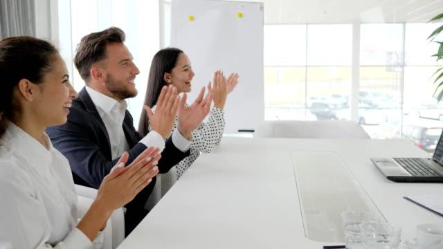 feliz-negocio-Grupo-Palmas-de-las-manos-en-cámara-lenta-aplaudan-empleados-de-oficina-colegas-cerca-de-escritorio