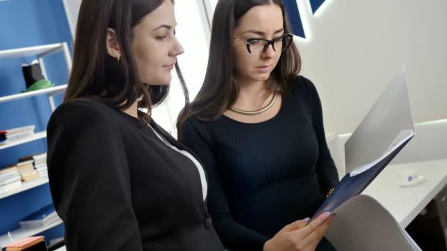 Dos-empresarias-mira-a-través-de-los-documentos-en-la-oficina
