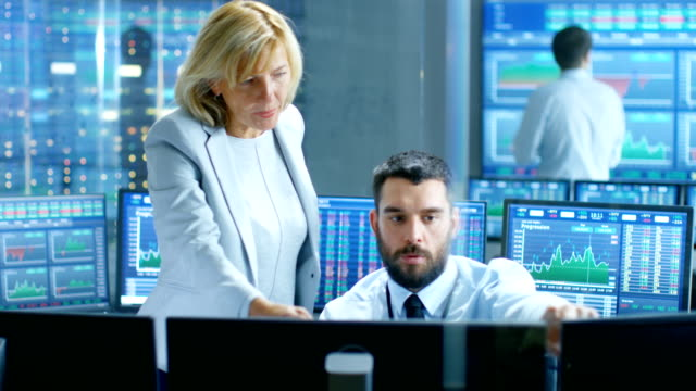 En-el-mercado-de-valores-la-firma-Director-Ejecutivo-habla-con-Trader-profesional-Está-rodeados-de-pantallas-con-gráficos-y-números-de-la-pizarra-