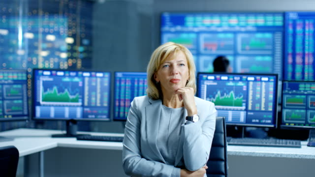 Stock-Market-Leading-Analyst-Thinking-Hard-on-Solving-Financial-Problem-Behind-Her-People-Working-and-Monitors-Show-Graphs-and-Figures-