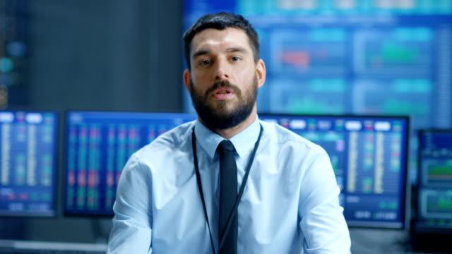 Trader-profesional-bolsa-carismáticamente-habla-a-la-cámara-Detrás-de-él-las-pantallas-de-ordenador-con-pizarra-números-datos-gráficos-