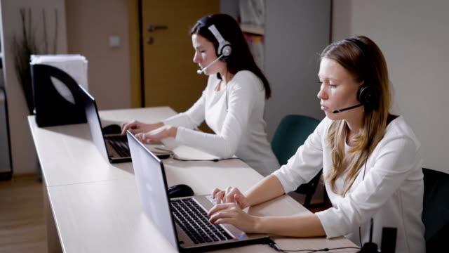 Varias-mujeres-impresión-el-texto-en-el-teclado-del-ordenador-portátil-la-charla-de-las-señoras-en-el-micrófono-en-la-oficina-de-centro-de-llamada-contestar-las-llamadas-entrantes-y-asesorar-a-los-clientes