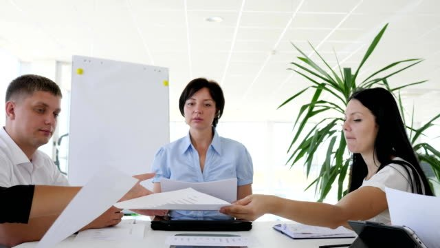 Business-meeting-of-collaborators-at-desk-with-documents-in-hand-in-boardroom