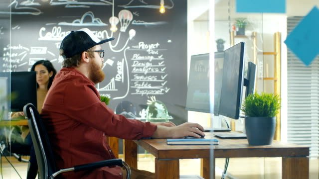 In-the-Creative-Agency-Videographer-in-a-Cap-Works-on-Personal-Computer-with-Two-Monitors-He-s-Doing-Video-and-Audio-Editing-Stylish-Coworkers-at-Their-Workstations-and-Chalkboard-Wall-Visible-