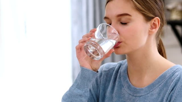 Beautiful-Woman-Drinking-Water-from-Glass-at-Home