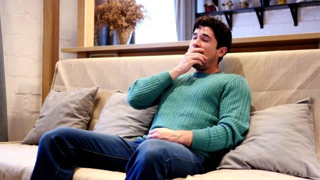Hombre-joven-cansado-bosteza-sentado-en-el-sofá-en-casa
