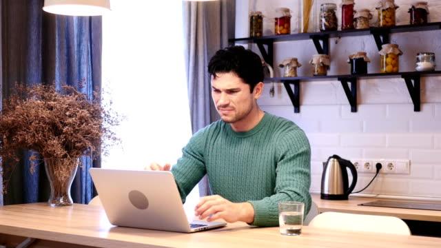 Depressive-Menschen-aufgeregt-durch-den-Verlust-an-Laptop-sitzen-in-der-Küche-arbeiten