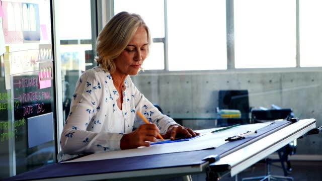 Mujer-arquitecto-trabajando-en-proyecto-sobre-elaboración-de-tabla-de-4k
