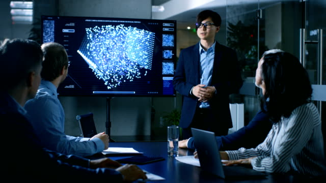 In-the-Conference-Room-Chief-Engineer-Presents-to-a-Board-of-Scientists-New-Revolutionary-Approach-for-Developing-Artificial-Intelligence-and-Neural-Networks-Wall-TV-Shows-Their-Achievements-