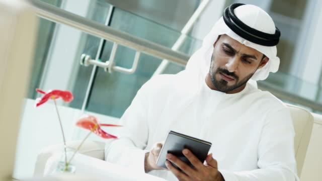 Arab-businessman-wearing-national-dress-using-tablet-technology
