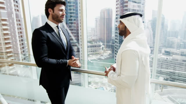 Middle-Eastern-and-Caucasian-businessmen-meeting-downtown-building
