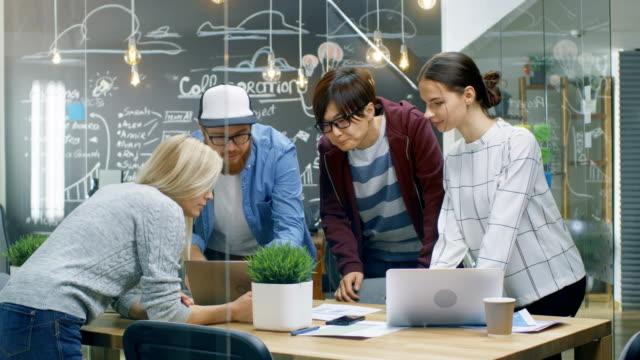 Reunión-del-equipo-de-desarrolladores-inclina-sobre-la-mesa-y-mira-los-resultados-mostrados-en-el-portátil-Jóvenes-creativos-en-el-entorno-de-oficina-con-estilo-