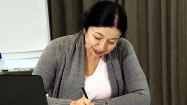 Empresaria-Senior-tomando-notas-mientras-trabaja-en-la-computadora-portátil