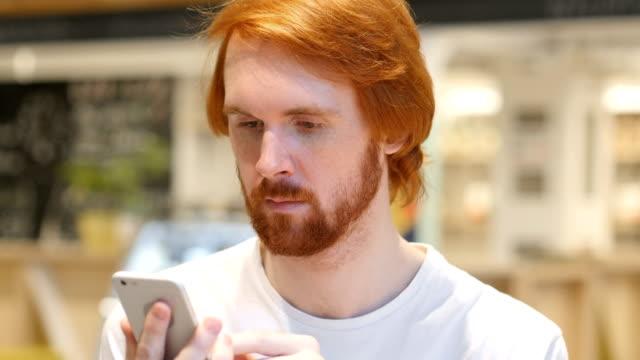 Redhead-Beard-Man-Using-Smartphone-for-Online-Browsing